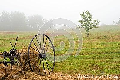 Hay rake in field in fog