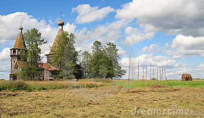 Haymaking near ancient wooden church