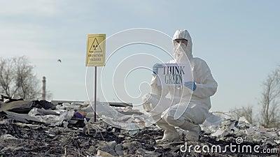 Hazmat生物学家到防护套服展示里签字认为绿色在垃圾场以尖在露天的辐射危害 股票录像