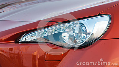Headlight of red car close up