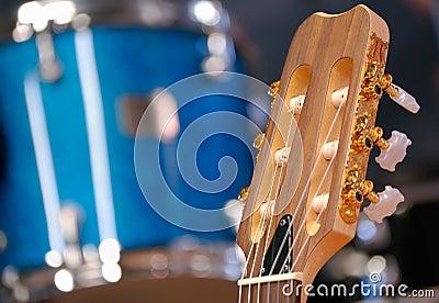 Headstock of guitar against drum.