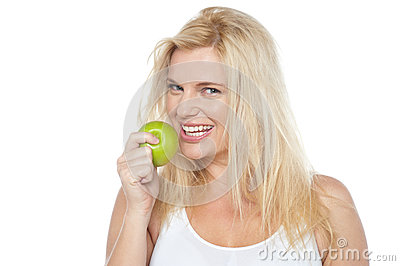Health conscious woman about to take bite from green apple