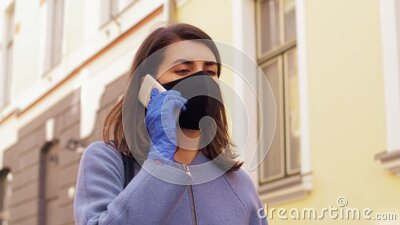 Woman in face mask calling on smartphone in city stock video footage