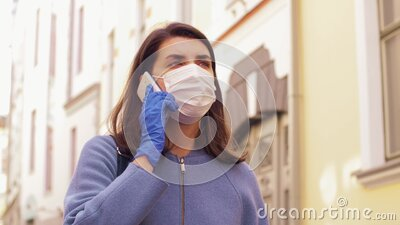 Woman in face mask calling on smartphone in city stock footage
