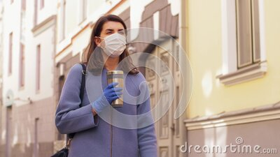 Woman in medical mask with tumbler walking in city stock video footage
