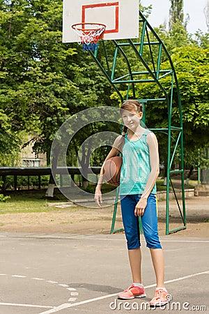 Healthy active teenage girl on a basketball court