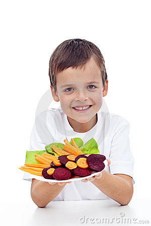 Healthy boy with fresh vegetables on plate
