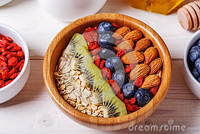 Healthy breakfast - bowl of oat flakes with fresh fruit, almond Stock Photo