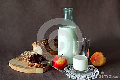 Healthy breakfast with fresh bread, smeared jam, a glass of milk and apples
