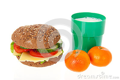 Healthy brown bread roll with fruit and milk