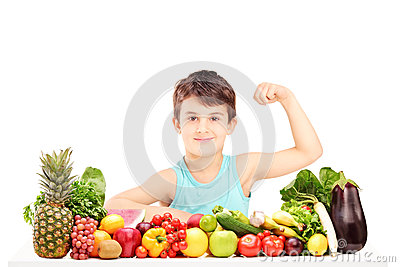 Healthy child showing his arm muscles and sitting on a table ful
