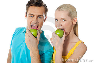 Healthy couple eating fresh green apple