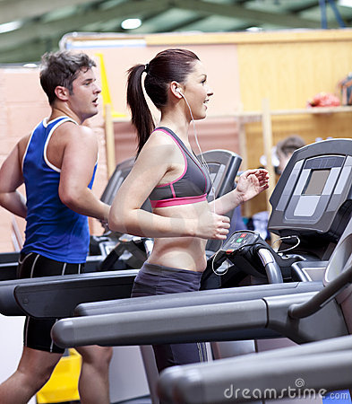 Healthy couple on a treadmill in a sport center