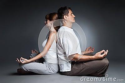 Healthy couple in yoga position on dark