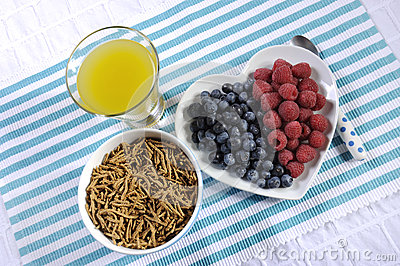 Healthy diet high dietary fiber breakfast with bowl of bran cereal and berries with pineapple juice - aerial
