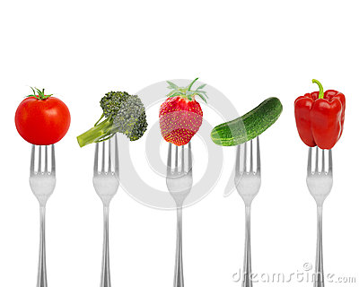 Healthy diet, organic food on forks with vegetables and berries. Stock Photo