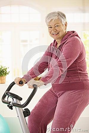 Healthy elderly woman on exercise bike