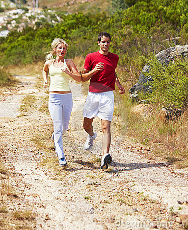 Healthy fit couple actively running outdoors