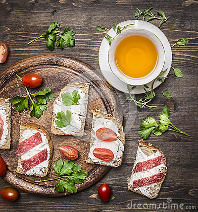 Free Healthy Foods Sandwiches With Red Fish, Cherry Tomatoes And Salami On A Cutting Board,  Cup Of Tea With Thyme On Wooden Rust Royalty Free Stock Image - 68689416