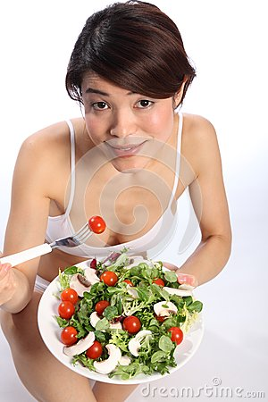 Healthy Japanese girl looks up eating green salad