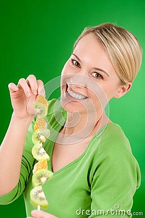 Healthy lifestyle - woman eating kiwi and orange