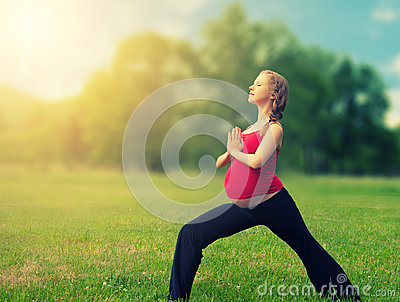 Healthy pregnant woman doing yoga in nature