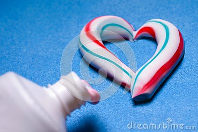 Healthy teeth. Hygiene of the oral cavity. Colored toothpaste from a tube. Pasta in the form of a heart Stock Photo