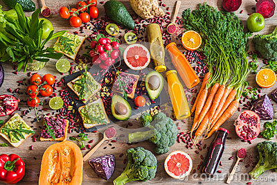 Healthy vegan food. Sandwiches and fresh vegetables on wooden background. Detox diet. Different colorful fresh juices. top view Stock Photo