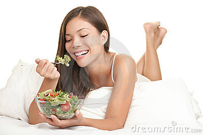 Healthy woman eating salad in bed