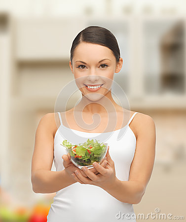 Healthy woman holding bowl with salad in kitchen