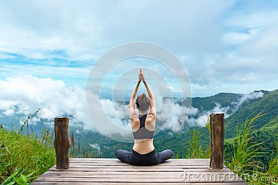 Healthy woman lifestyle balanced practicing meditate and zen energy yoga on the bridge in morning the mountain nature Stock Photo