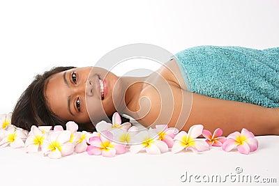 Healthy woman in spa amongst frangipani flowers