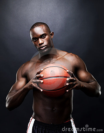 Healthy young man holding a basketball tightly