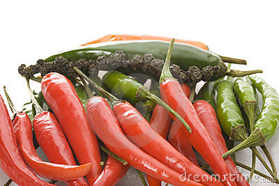 Heap of ripe chilli peppers on a white background