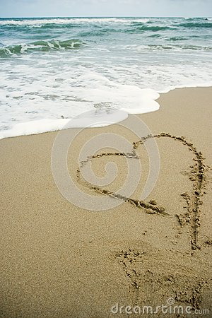 Heart drawing on the sand beach