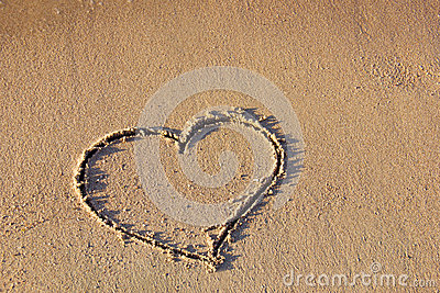Heart drawing in the sand on the beach
