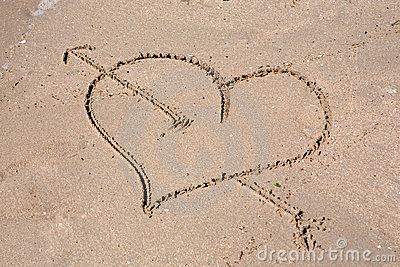 Heart engraved on the wet sand