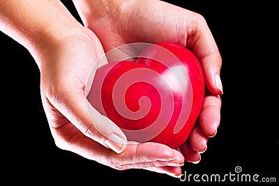 Heart in hands over black background