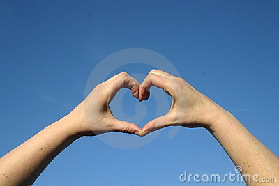 Heart of love with hands in blue sky