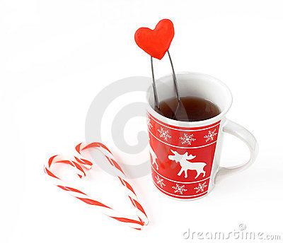Heart made from christmas candies and cup of tea