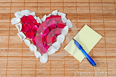 Heart made of rose petals, blank note and pen