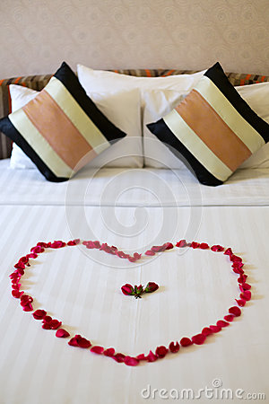 Heart of rose petals laid out on the bed