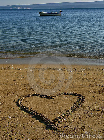 Heart in the sand, boat at sea