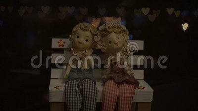 Heart Shaped Bokeh Around Puppets. Subject: Boy and girl doll with the heart shaped bokeh in the background. Shot: Bokeh, Blurred Background stock footage