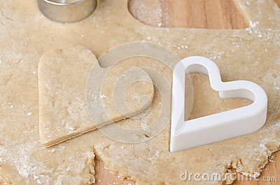 Heart shaped cookie cutter on raw cookie dough and a heart-shape