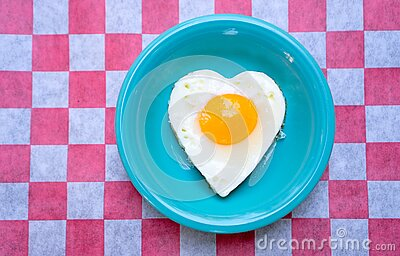 Heart-shaped grilled egg on a teal plate. An egg, fried sunny side up and heart-shaped, on a teal plate that sits on a white and red checkered paper royalty free stock photography
