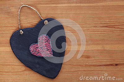 Heart shaped slate on wooden background.