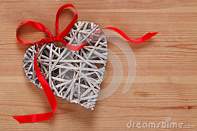 Heart shaped wicker decoration with red ribbon.