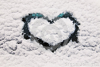 Heart symbol on snowy glass