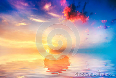 Heart shape in calm ocean at sunset. Beautiful sky